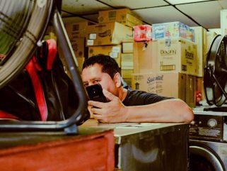 man in black shirt holding smartphone near desk fan
